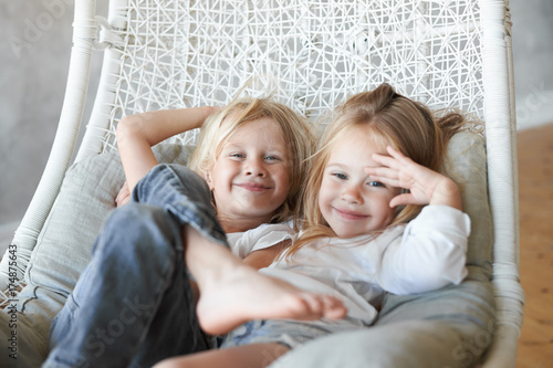 Fototapeta Picture of two siblings spending time together: blonde cute boy sitting in wicker hanging chair with his adorable little sister, both children looking at camera and smiling. Happy family and childhood obraz