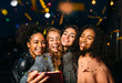 canvas print picture Group of happy women taking selfie on mobile phone, standing outdoors at night