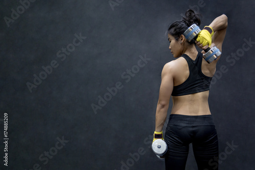 Obraz Young Asian woman lifting dumbbell in weight training fitness gym, sport exercise and muscular build, healthy lifestyle - fototapety do salonu