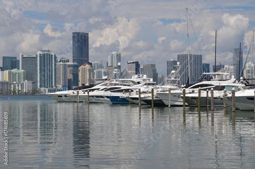 Fototapeta Szeroki wybór łodzi rekreacyjnych zacumowany przy marinie Key Biscayne z condo Miami i panoramą handlową budynku w tle.