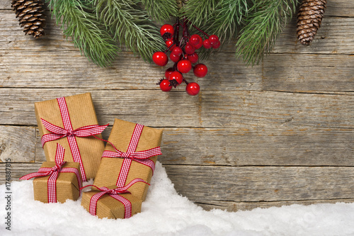 christmas gifts on snow wooden background