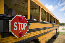 A Red Stop Sign With Lights On The Side Of An Old Yellow School Bus. Back To School