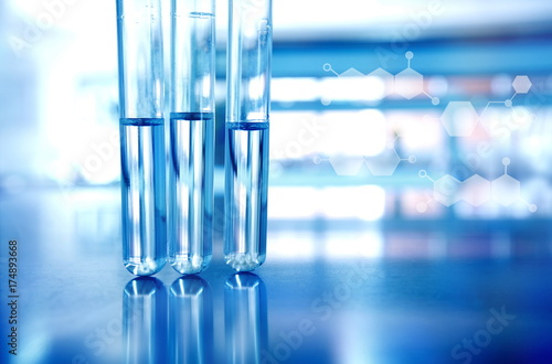 three test tubes with blue in technology science laboratory with chemical structure background