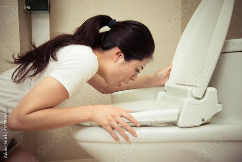 Fotografie, Obraz closeup of young pretty woman vomiting into toilet