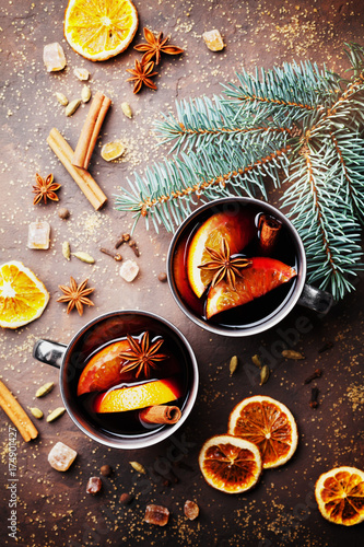 Two mugs of christmas mulled wine or gluhwein with spices and orange slices on rustic table top view. Traditional drink on winter holiday. Vintage toned.