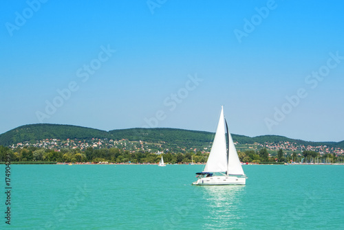 Fotografie, Obraz  A view from a ship to bright Balaton lake water and a white yacht with a town, forest and mountains at the background on sunny summer day, Hungary