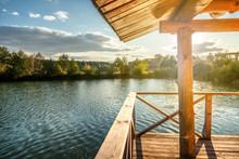Wooden House With A Terrace On The Water At The Lake, At Sunset, A Beautiful River Bank At Sunset