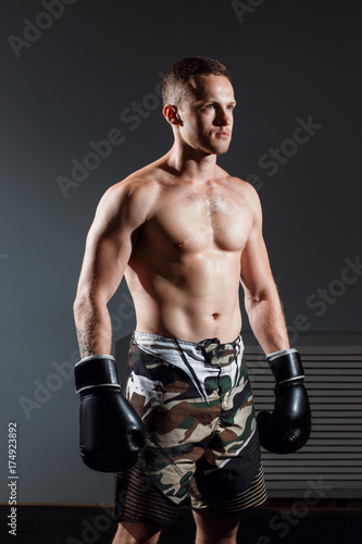Photo handsome man or healthy boxer or Thai boxer with six pack wearing boxing gloves