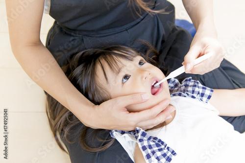Fotografia  母に歯を磨いてもらう幼い女の子