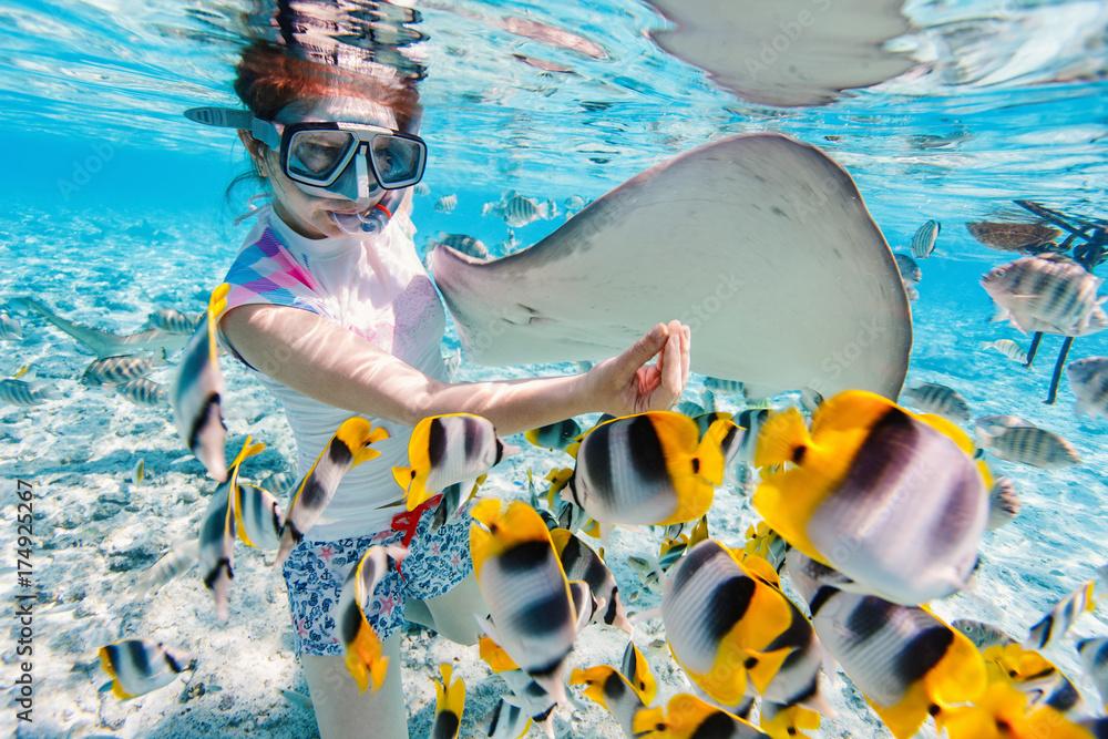 Fototapeta Woman snorkeling with tropical fish
