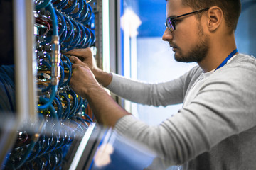 Young man connecting cables in server room