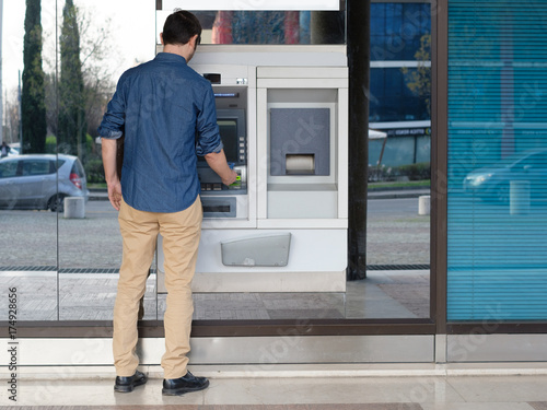 Fotografia, Obraz Man hand inserting a credit card in an atm