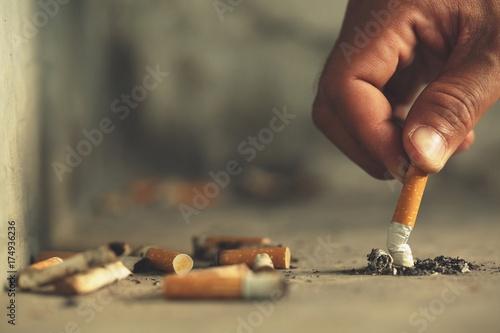 Fotografija  Hand putting out a cigarette,cigarette butt on Concrete floor, bare cement