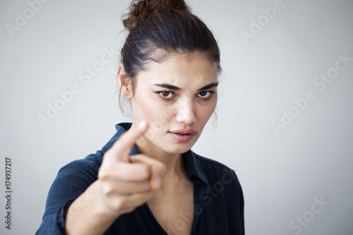 Fotografía  Angry woman pointing isolated on gray background