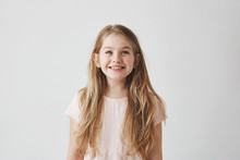 Portrait Of Cute Little Girl With Long Light Hair Smiling Brightfully, Looking Upside On Colorful Flying Balloons With Happy And Excited Expression.