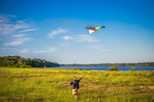 Child Flying Kite In Meadow