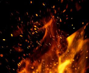 Fototapeta na wymiar flame of fire with sparks on a black background