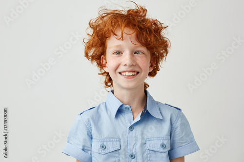 Valokuva  Close up portrait of funny little boy with orange hair and freckles mowing eyes,