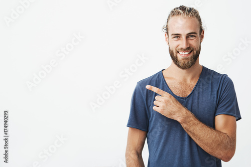 Happy beautiful bearded guy with good-looking hairstyle looking at camera, smiling and pointing aside with hand Wallpaper Mural