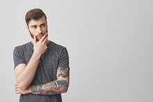 Portrait Of Beautiful Serious European Man With Beard And Tattoo On Arm Holding Hand In Face, Looking Aside With Thoughtful Expression Trying To Remember Actor Name.