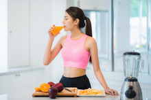Asian Lady In Fitness Sport Wear Drink A Mix Fruit And Vegetable