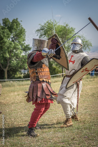Fotografía  Medieval knight battle with swords and shields, reenactment with costumed characters and medieval armor with chainmail, helmet swords and shields