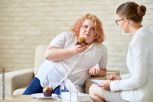 Fotografie, Obraz  Portrait of overweight young woman  eating cupcakes during therapy session with