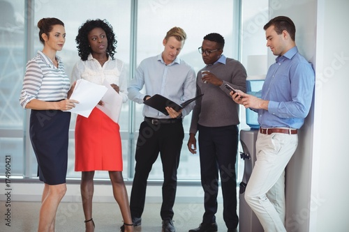 Fototapety, obrazy: Young business colleagues discussing by water cooler