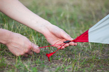 Close-up Of Girl Hands Fastens A Tent For Camping Pegs