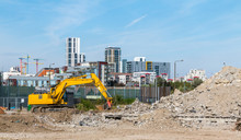 A Yellow Digger Works On The Demolition Site On Greenwich Millennium Leisure Park. Surrounded By The High Rise Blocks And Concrete Rubble Pile