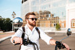 Cool bearded man in sunglasses with backpack rides