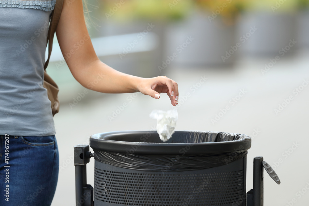 Fototapeta Civic woman throwing garbage in a trash bin