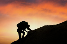 A Silhouette Of Man Climbing On Rock, Mountain At Sunset,Despite The Many Obstacles We Will Keep Going Highest Goals Expected As Until It Succeeds.