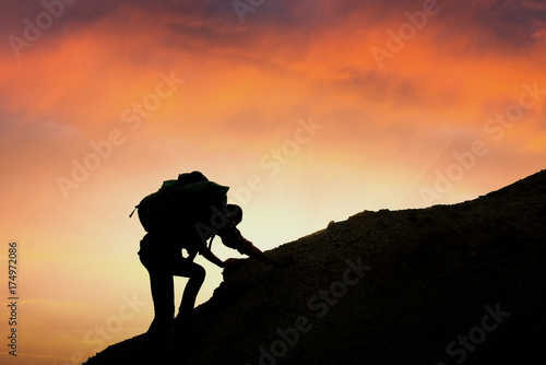 A silhouette of man climbing on rock, mountain at sunset,Despite the many obstacles we will keep going highest goals expected as until it succeeds Canvas Print