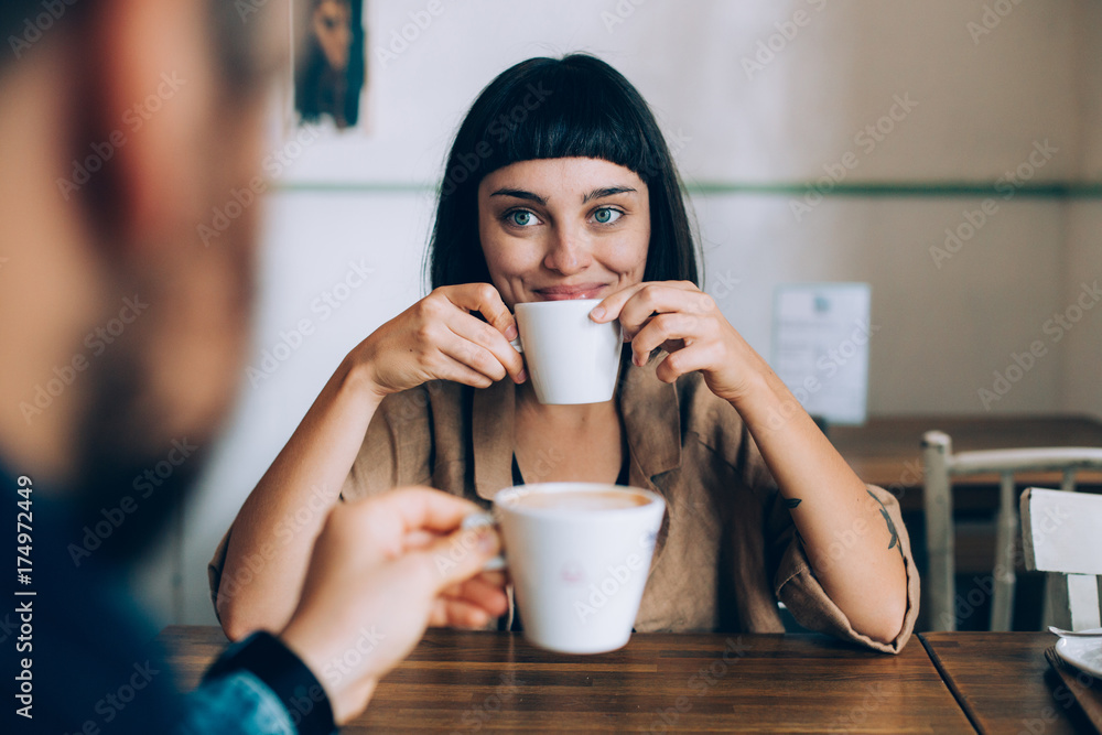 Fototapety, obrazy: Happy romantic couple on date, drink warm coffee with milk, she looks lovingly at her boyfriend or partner, smiles and spark in her eyes. early morning family routine