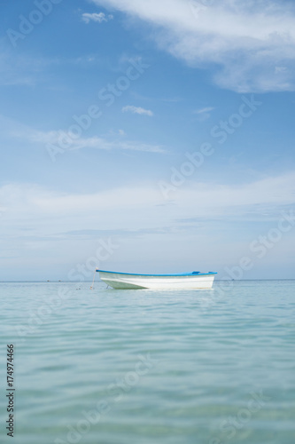 Tuinposter Schipbreuk Small single fishing boat floating on the calm sea over blue sky background