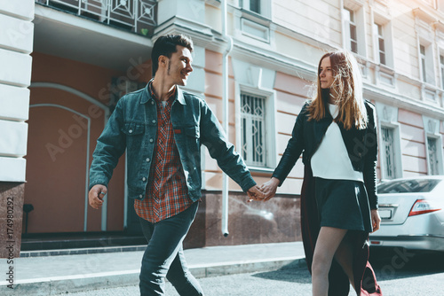 Fotografia  Young couple lovers walking in city, fooling around and enjoying sunny day