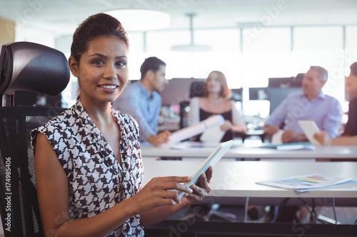 Fototapeta Portrait of businesswoman using digital tablet in office