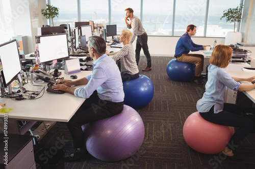 Fotografía  Business people sitting on exercise balls while working in