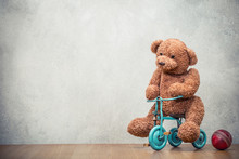 Teddy Bear Riding Retro Toy Trike And Old Leather Ball Front Concrete Wall Background. Vintage Style Filtered Photo