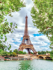 FototapetaClassic view on Eiffel Tower through green poplar foliage over Seine river in Paris. Beautiful summer morning scenery. Vertical orientation. Eiffel Tower is famous travel destination in Europe.