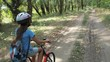 Child with a bicycle in nature. A little girl in a helmet is riding a bicycle in the forest.