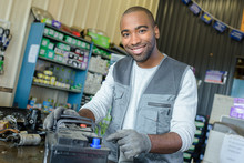 Male Mechanic With Used Vehicle Battery On Shop Counter
