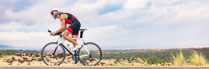 Triatlon biciklistički čovjek vozi bicikl na cestovnom biciklu u pozadini natpisa u prirodi. Triatlonac biciklista koji vozi bicikl u Ironman konkurenciji. Obrezivanje zaglavlja Panorama za pejzažni prostor za kopiranje.