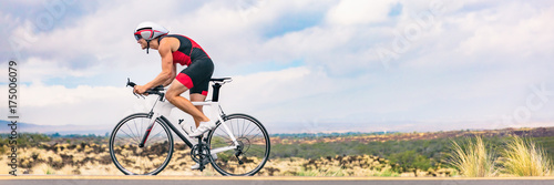 Foto auf Gartenposter Radsport Triathlon biking man cycling on road bike in nature background banner. Cyclist triathlete riding bicycle in ironman competition. Panorama header crop for landscape copy space.