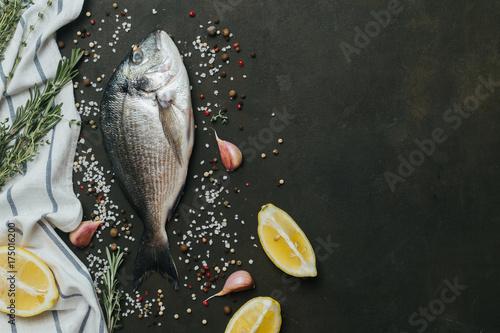 Fotografie, Obraz  Fresh Dorado on black slate stone board with spices, herbs, lemon and salt