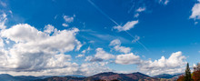Beautiful Cloudscape Over The Mountain Ridge. Lovely Nature Background With Blue Sky And Fluffy Clouds On Autumn Day