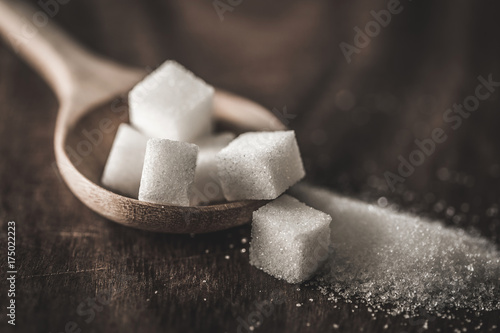 Fotografia, Obraz Close up the sugar cubes and cane in wooden spoon on the table ,retro color tone