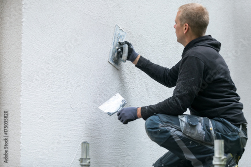 Fotografía  construction worker putting decorative plaster on house exterior
