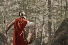 Back View Of Man In Gladiator Helmet And Red Long Cloak Standing With Round Shield And Spear In Hands Looking Away In Woods. Spartan.